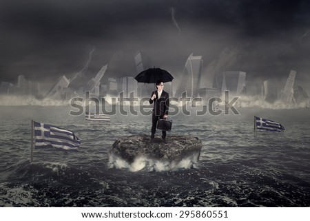 Businessman standing on the rock while holding umbrella with the city and Greek flag sinking on the sea