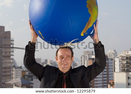 Businessman standing on the roof of a building with the city in the background holding a large globe in one hand. - stock photo