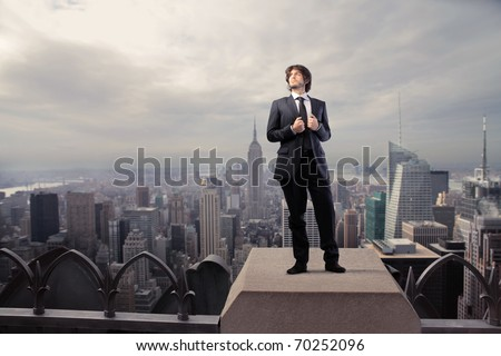 Businessman standing on the rooftop of a skyscraper - stock photo