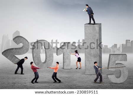 Businessman standing on the top bar and using a megaphone for yelling and commanding his employees compose number 2015 - stock photo