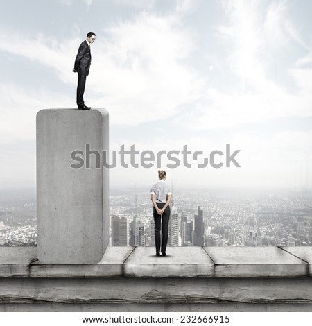 Businessman standing on top and looking down at colleague