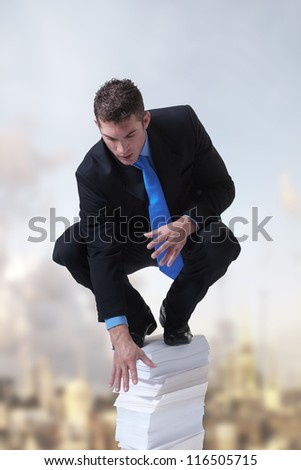 businessman standing on top of a pile of paper against a city backdrop - stock photo