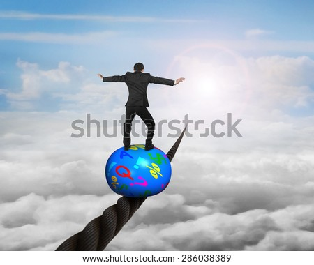 Businessman standing on top of colorful symbols ball, balancing on a wire, with sky sun cloudscape background. - stock photo