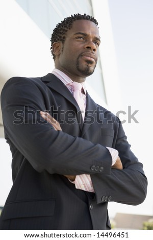 Businessman standing outdoors by building - stock photo