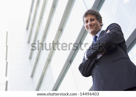 Businessman standing outdoors by building smiling - stock photo