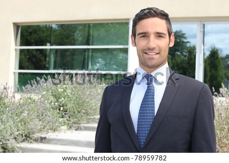 Businessman standing outside a modern house - stock photo