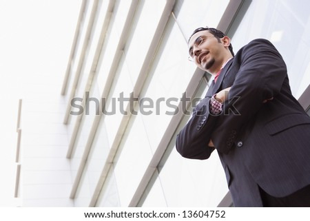 Businessman standing outside modern office building - stock photo