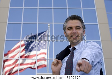 Businessman standing outside the office building with the American flag reflection in the windows - stock photo