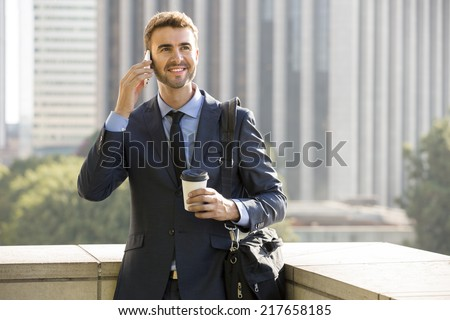 Businessman standing outside the office on the phone with coffee - stock photo