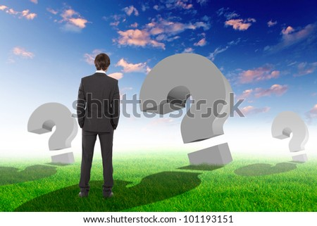 Businessman standing outside with question marks around him - stock photo