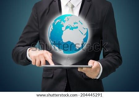 Businessman standing posture hand hold globe map on tablet isolated on dark background - stock photo