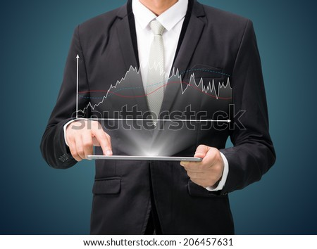 Businessman standing posture hand hold graph on tablet isolated on dark background - stock photo