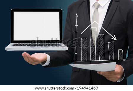 Businessman standing posture hand hold laptop showing graph isolated on dark background - stock photo