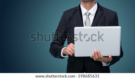 Businessman standing posture hand hold notebook laptop isolated on dark background - stock photo