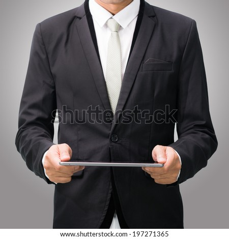 Businessman standing posture hand holding blank tablet isolated on over gray background
