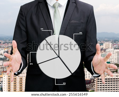 Businessman standing posture hand holding graph finance on City background - stock photo