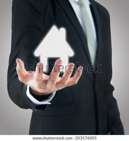 Businessman standing posture hand holding house icon isolated on over gray background