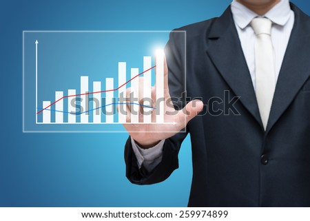 Businessman standing posture hand touch graph finance isolated on blue background - stock photo
