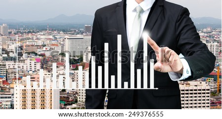 Businessman standing posture hand touch graph finance on City background - stock photo