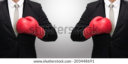 Businessman standing posture in boxing gloves isolated on over gray background