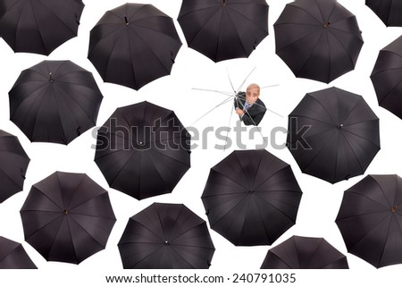 Businessman standing shelter less with old umbrella amongst black umbrellas isolated in white - stock photo