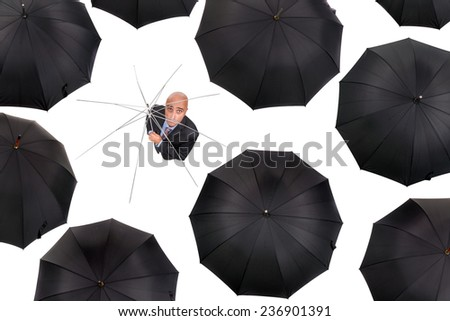 Businessman standing shelterless with old umbrella amongst black umbrellas isolated in white - stock photo