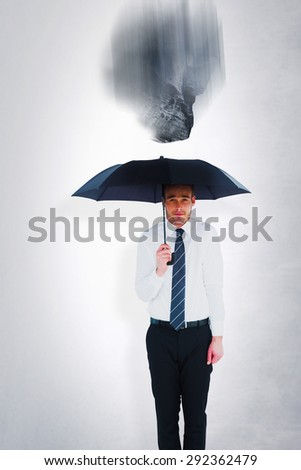 Businessman standing under black umbrella against grey room
