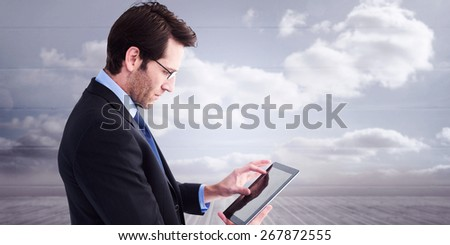 Businessman standing while using a tablet pc against clouds in a room - stock photo