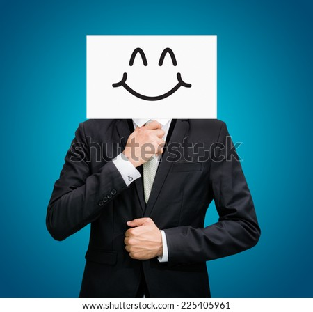 Businessman standing white paper happy smile face holding front of head on blue background - stock photo