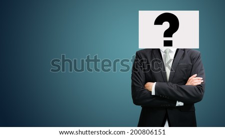 Businessman standing white paper ideas face holding front of head on dark background - stock photo