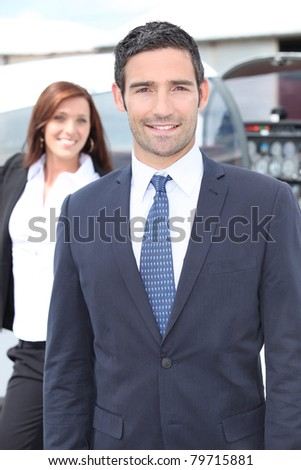 Businessman standing with a woman and light aircraft - stock photo
