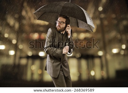 Businessman standing with an umbrella - stock photo