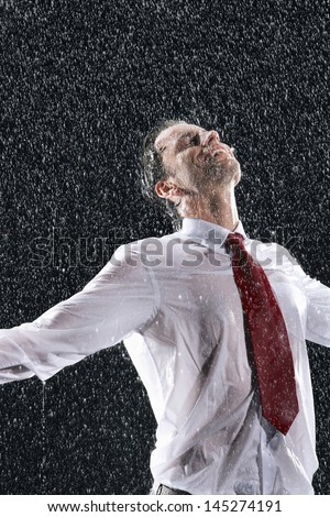Businessman standing with arms outstretched and eyes closed in the rain - stock photo