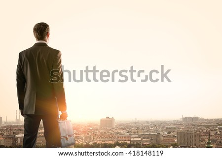 Businessman standing with back against morning city, panoramic view - stock photo