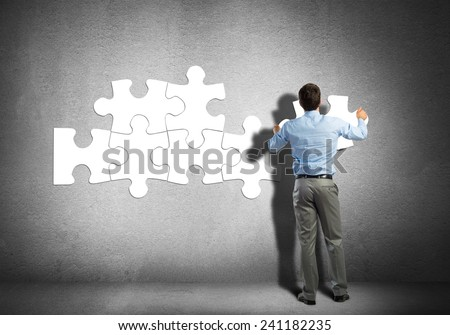 Businessman standing with back and connecting puzzles - stock photo