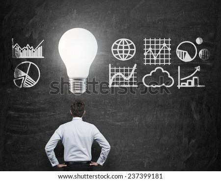 businessman standing with bulb over head - stock photo