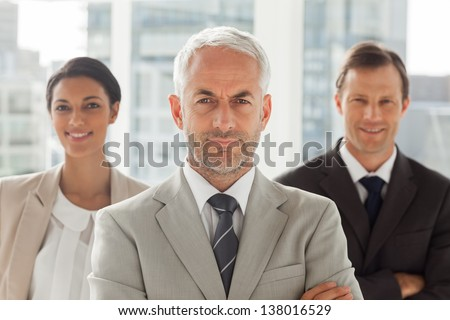 Businessman standing with colleagues behind with arms crossed - stock photo