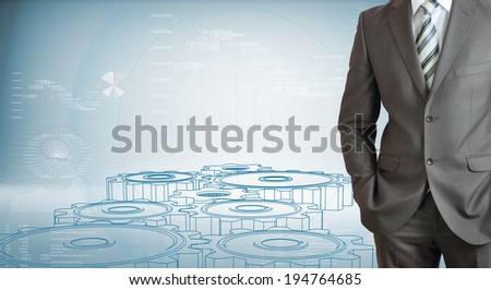 Businessman standing with hands in pockets. High-tech wire frame gears and graphs at backdrop - stock photo