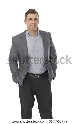 Businessman standing with hands in pockets, smiling.
