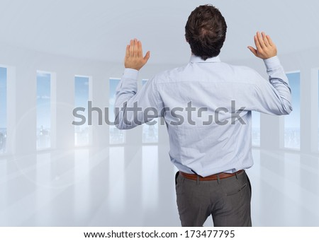 Businessman standing with hands up against bright white room with windows