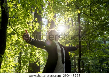Businessman standing with his arms outspread showing thumbs up sign celebrating business success in woodland with fresh green leaves on the trees backlit by the rays of the sun, low angle view. - stock photo