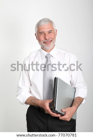Businessman standing with laptop computer - stock photo