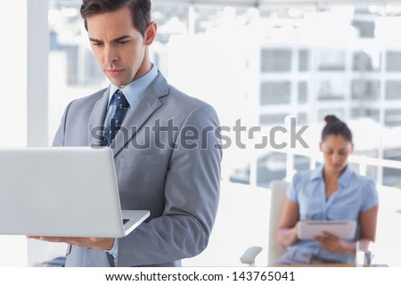 Businessman standing with laptop with woman working behind him