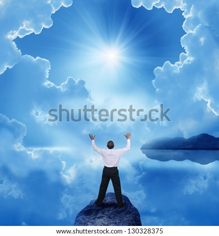 businessman standing with open arms on a rock - stock photo