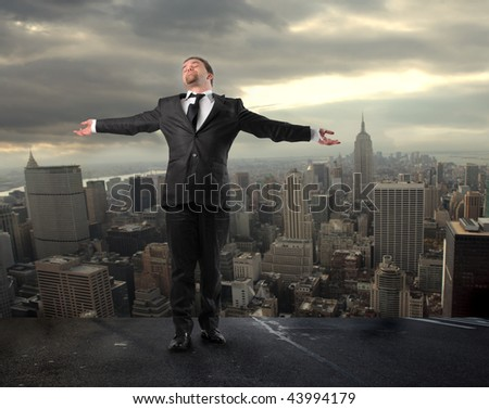 businessman standing with open arms on the top of ny city - stock photo