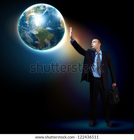 Businessman standing with our planet Earth. Elements of this image are furnished by NASA - stock photo