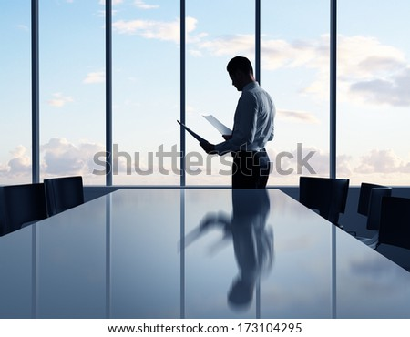 businessman standing with paper in office - stock photo