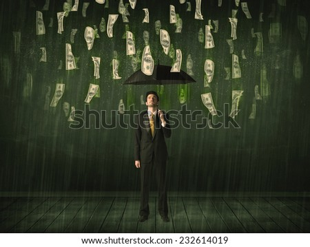 Businessman standing with umbrella in dollar bill rain concept on background - stock photo