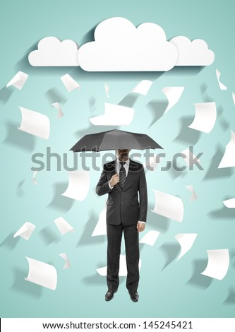 businessman standing with umbrella with flying around paper