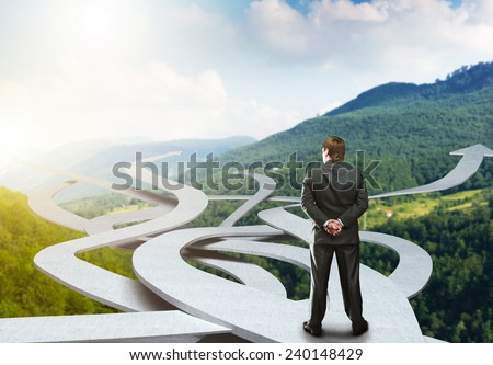 Businessman stands choosing his way